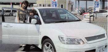 車の横でポーズをとっている青いぽすと記者
