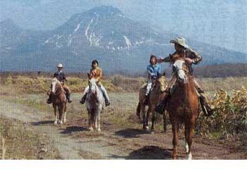 駒ケ岳をバックに乗馬体験をしている青いぽすと記者