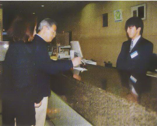 湯の川プリンスホテル渚亭のフロントでチェック飲する夫婦
