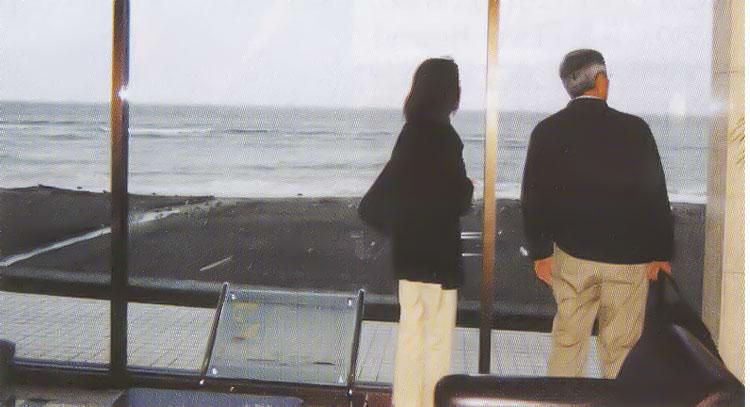ロビーの窓から海を見る夫婦