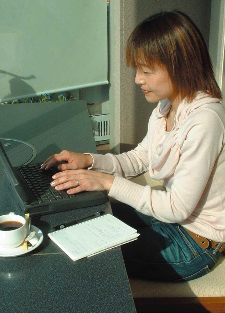 ノートパソコンを使ってDTPを行っている女性編集者