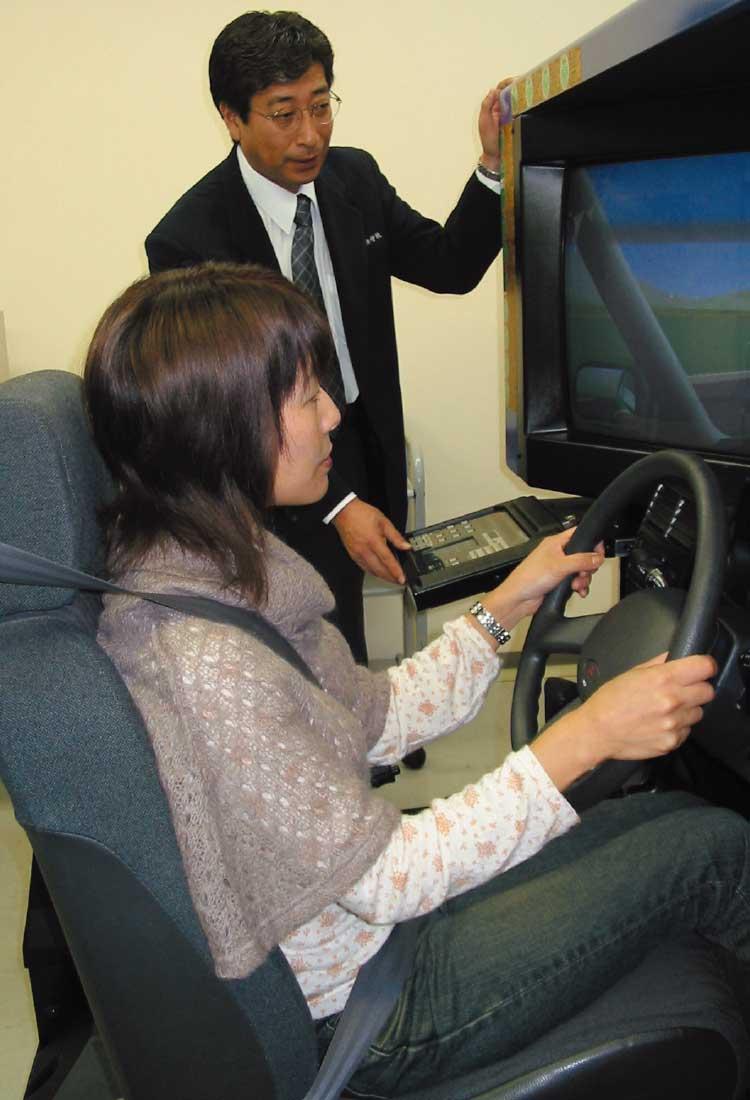 運転シミュレーターで講師から講習を受けている女性