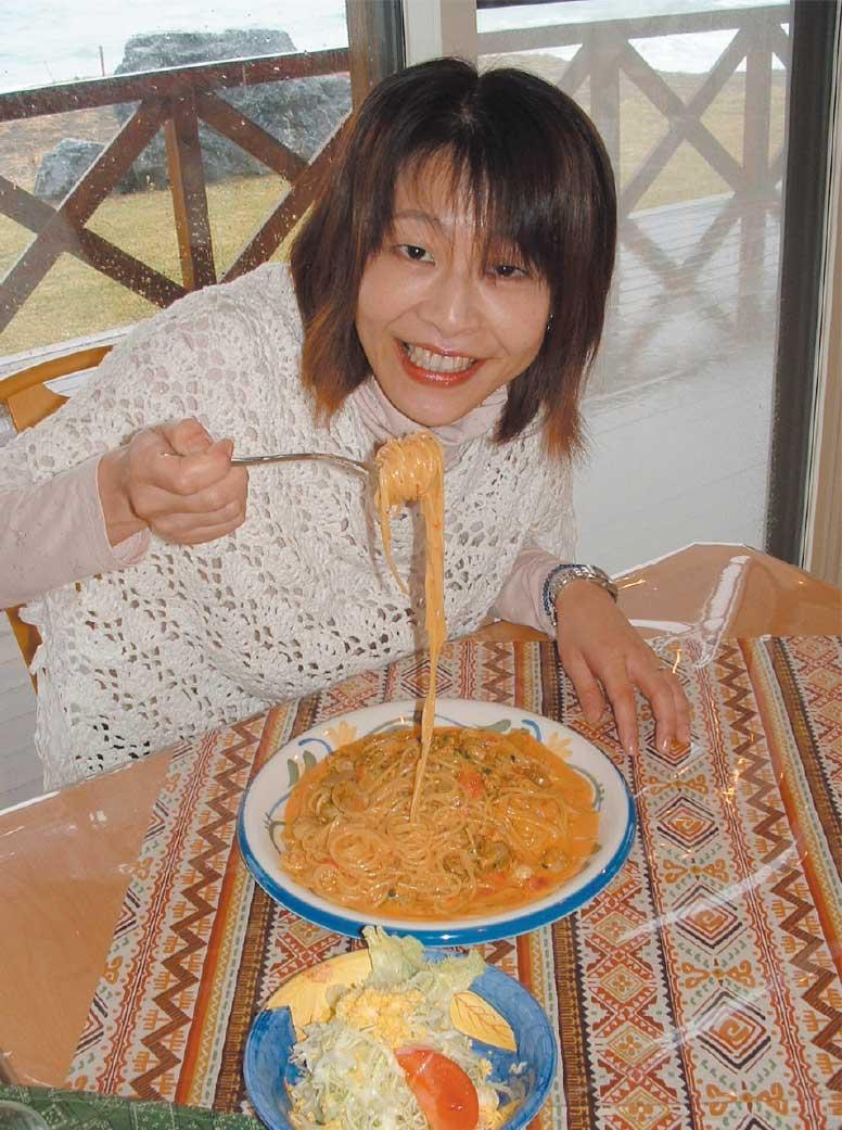 パスタを食べている青いぽすと女性記者