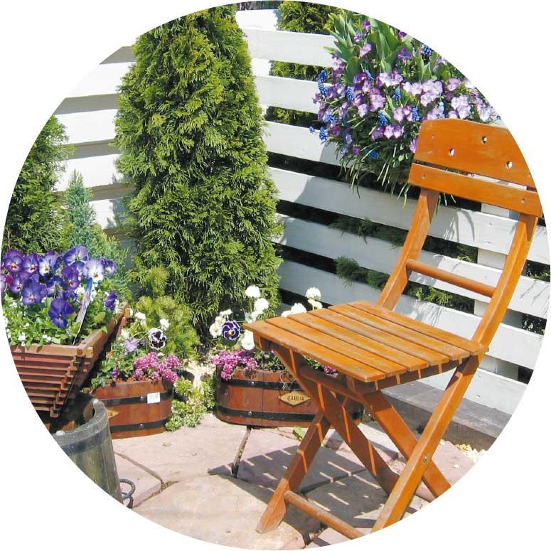 プランターボックスとハンギングバスケットの横に置かれた木の椅子