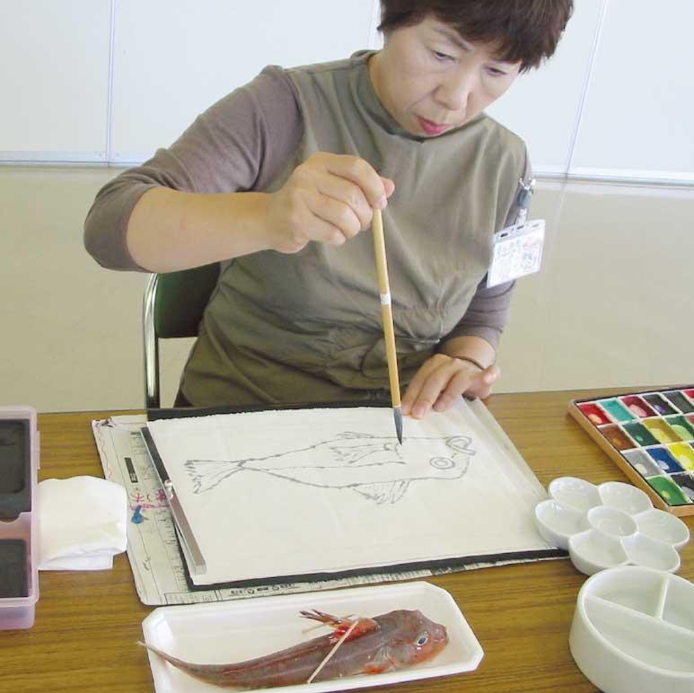 絵てがみサークル赤いポストで絵を描いている女性