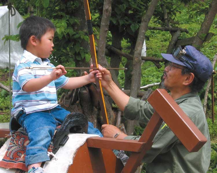 どさんこファームで流鏑馬のやり方を教わっている男の子