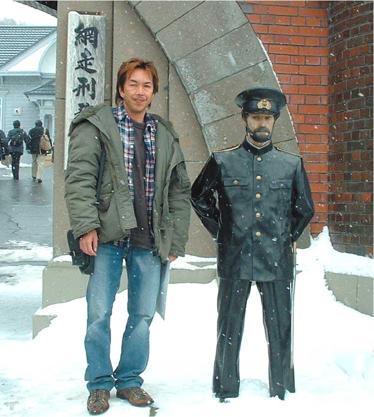 網走刑務所前で記念撮影する青山編集長