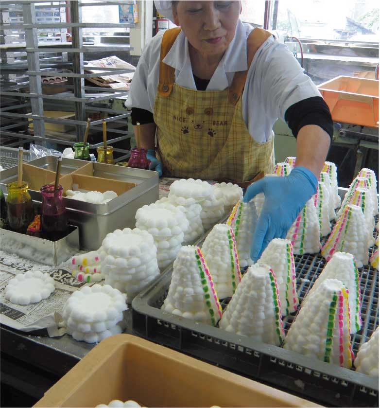 吉田食品工場で落雁に色づけをしている女性