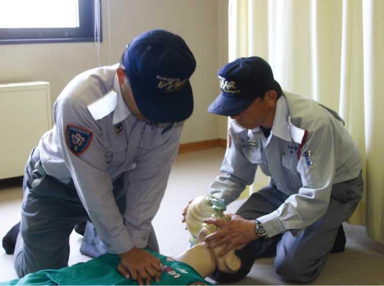 心臓マッサージ、手動式人工呼吸器を口に当ててる救急救命士たち