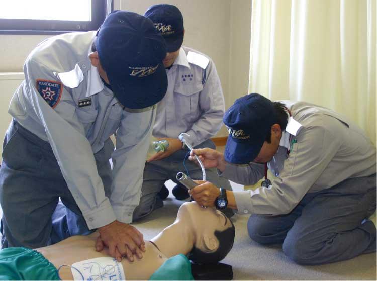 心臓マッサージ、口の中を確認している救急救命士たち