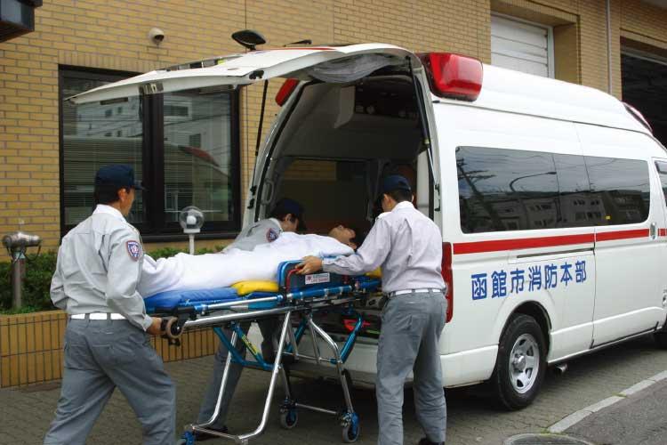 救急車に患者を入れようとしている救急救命士たち