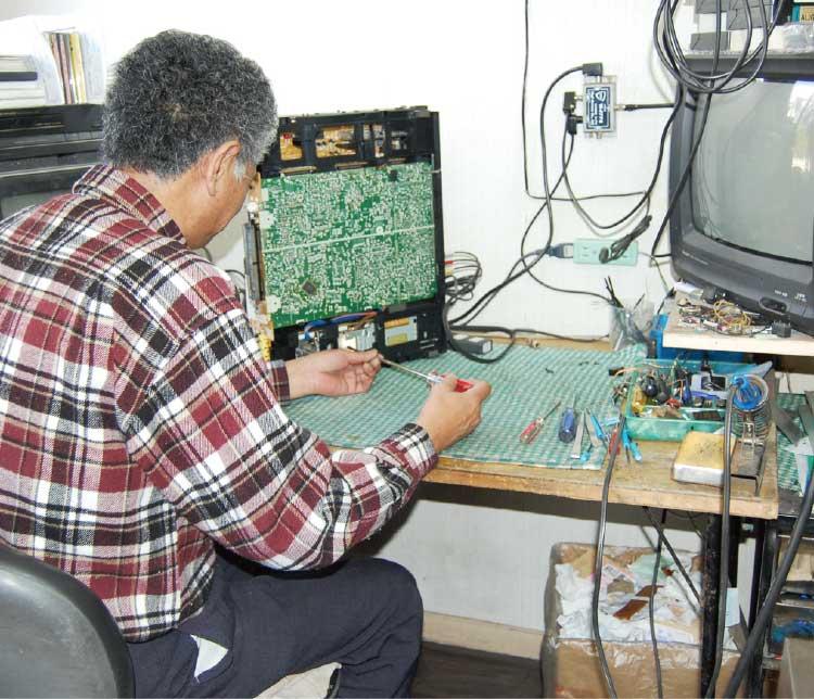 テクニカルショップイシイでテレビの修理をしている男性