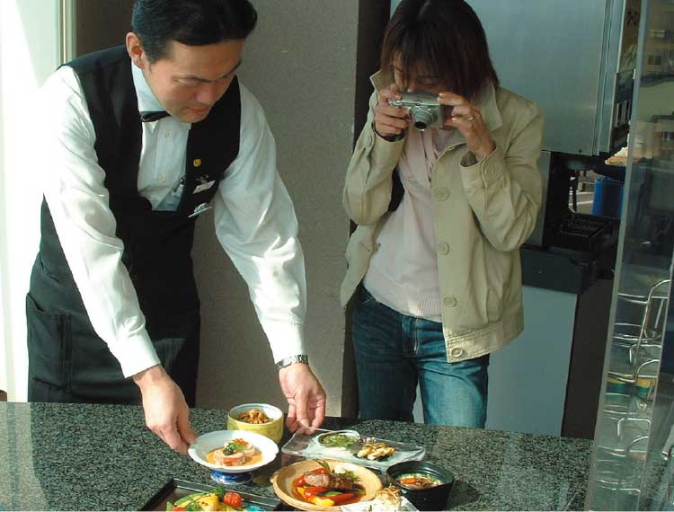 料理の写真を撮っている男性編集者