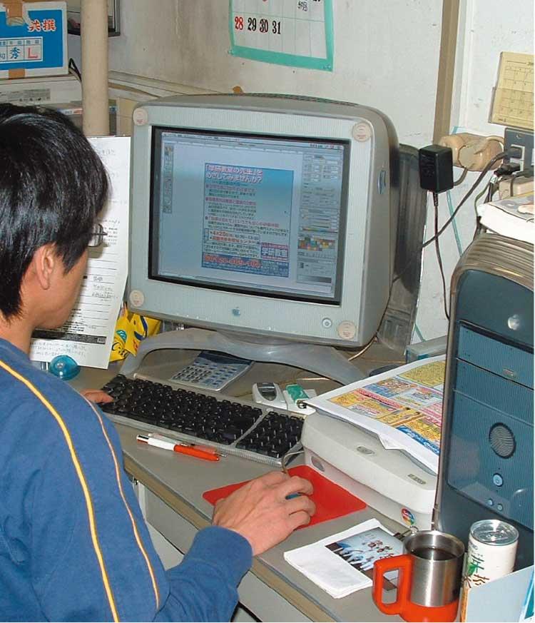 macを使って青いぽすと誌面を作成している男性編集者