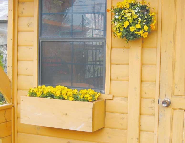 玄関ドアの横につけたハンギングバスケットと窓の下に設置されたプランターボックス