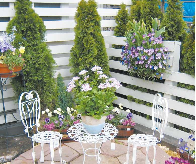 ベランダスペースに沢山の草花に囲まれて置かれた白い椅子とテーブル