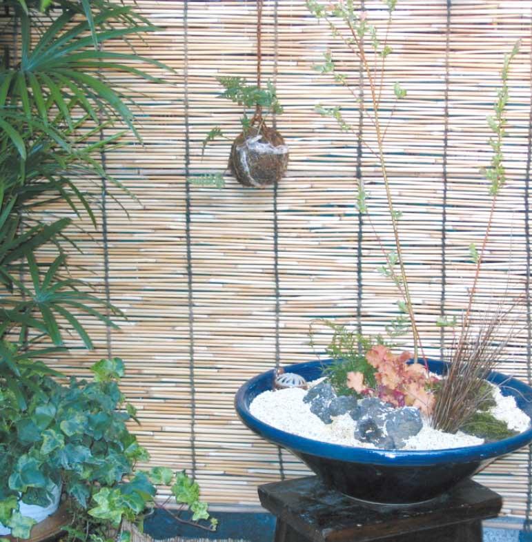 簾で仕切られた空間に設置された苔玉と陶器を使った生花風の観葉植物