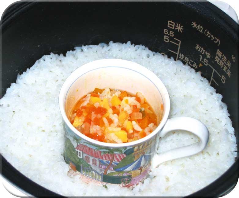 炊飯器の中のご飯の上にのってる離乳食の入ったカップ