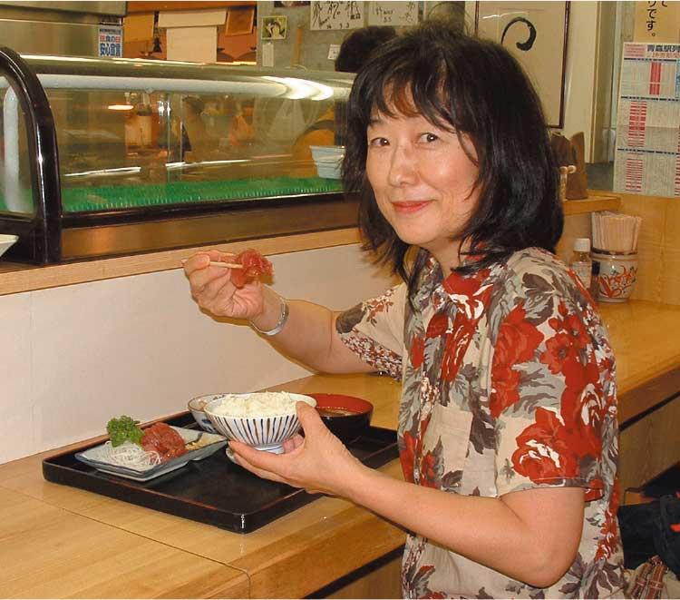 刺身を食べている女性記者