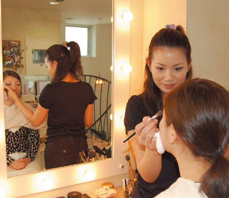 鏡の前で女性にメイクをしているプロのメイクアップアーティスト