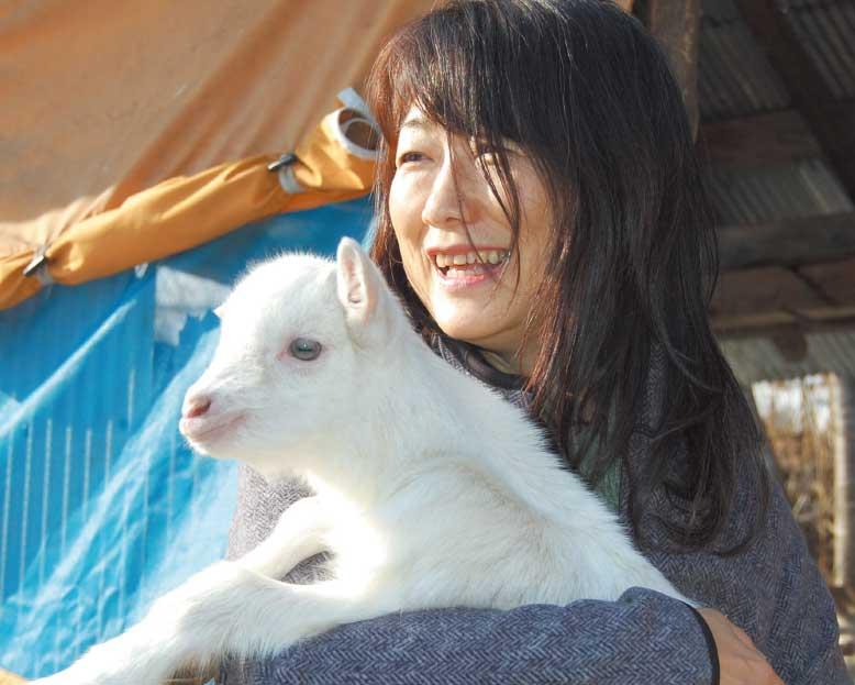 山田農場チーズ工房の子ヤギと写真を撮る女性