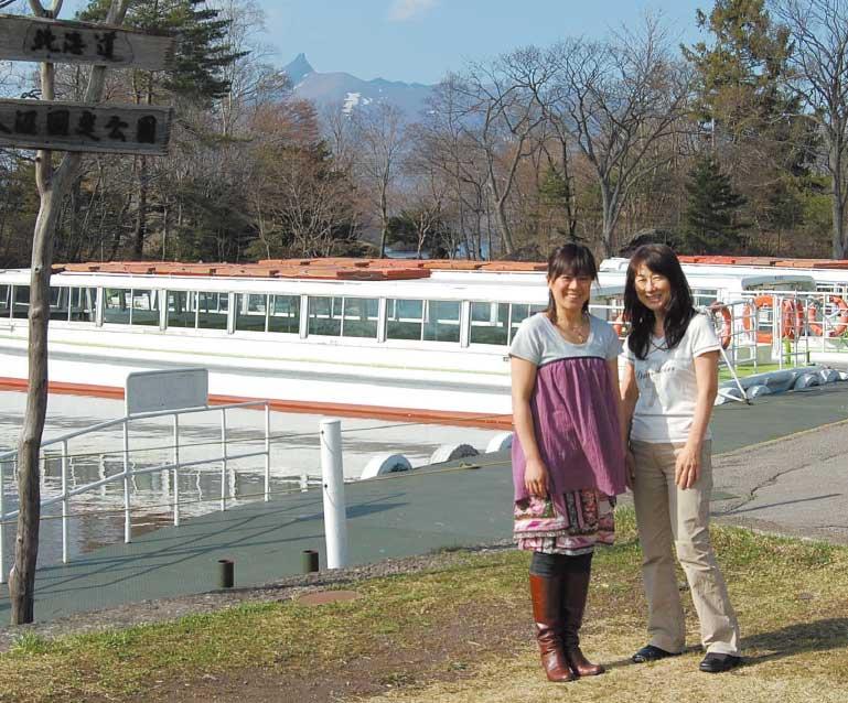 大沼の遊覧船乗り場で記念撮影している女性たち