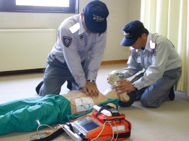 AEDを準備しつつ心臓マッサージを続ける救急救命士たち