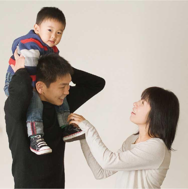 父親に肩車されてる男の子を見上げる母親