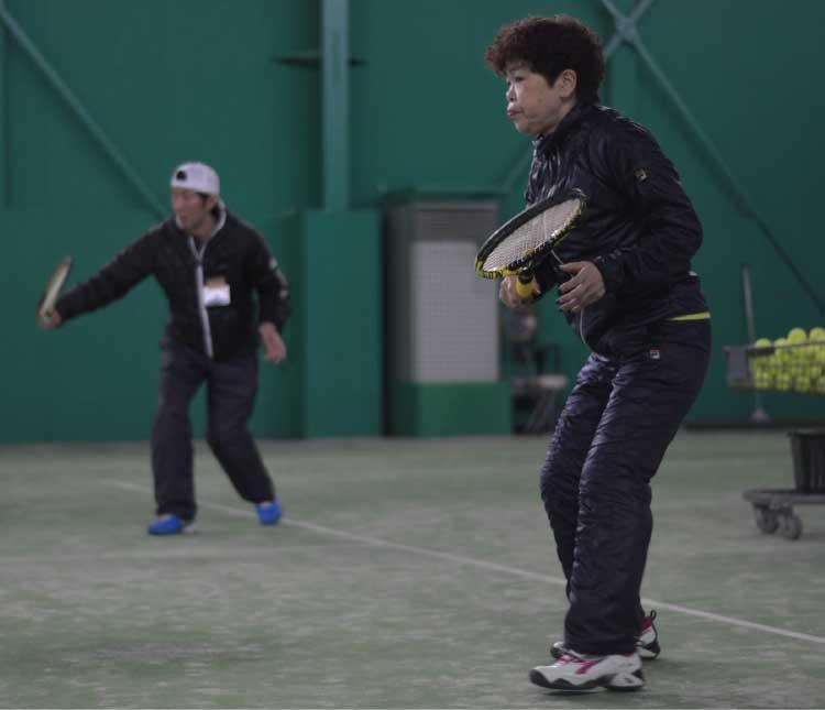 アクティブテニスでレッスンを受けている女性